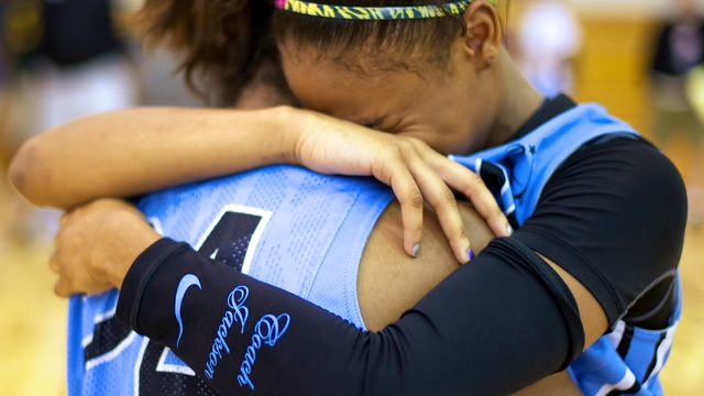 Moriah Jefferson, an homage to her fallen coach on her sleeve, shares tears with a teammate.