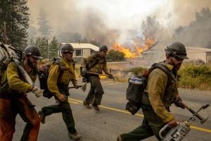 Firefighters flee as the Twisp River fire advances unexpectedly near Twisp, Washington, August 20, 2015.  (Reuters/David Ryder)
